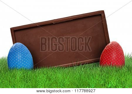 Easter eggs and chocolate bar on grass on white background