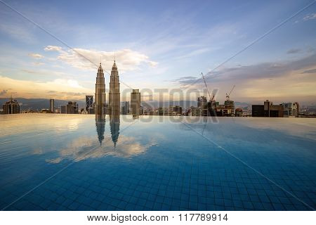 Beautiful reflection of Petronas Twin Tower in Kuala Lumpur city centre by the poolside at sunset.