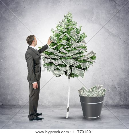 Businessman collecting money from tree