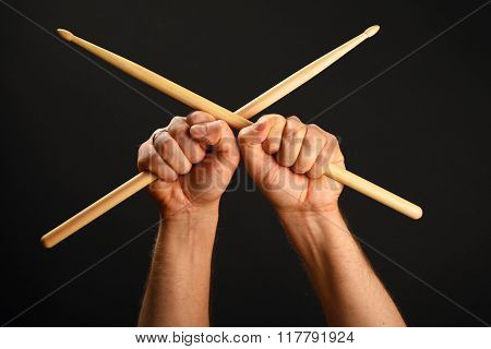 Two Hands With Crossed Drumsticks Over Black