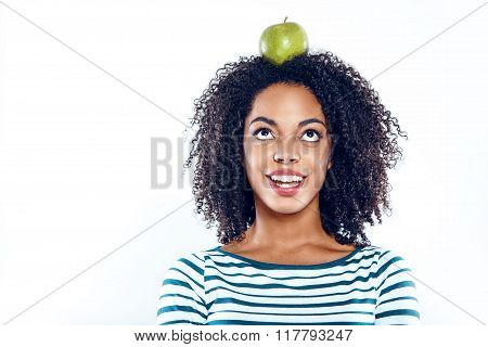 Bright portrait of beautiful young mixed race woman with curly hair on white background. Girl looking up and holding green apple at head