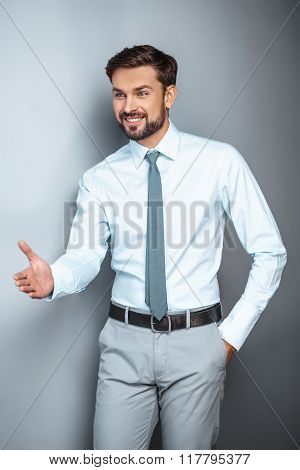 Studio shot of young attractive businessman. Businessman smiling and proposing to shake hand