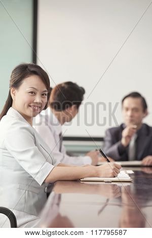 Businesswoman in Meeting Smiling At Camera