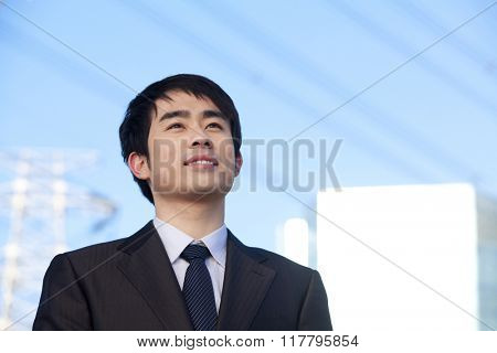 Businessman in Front of Power Lines