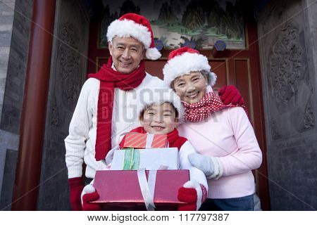 Family holding Christmas Gifts