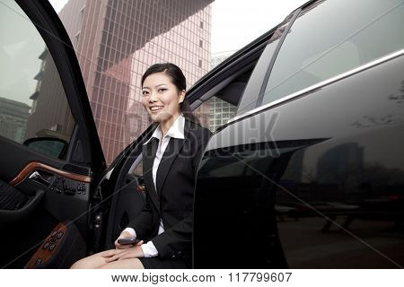 Businesswoman exiting a car