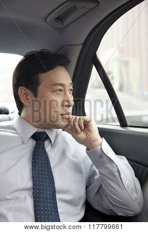 Businessman looking out car window