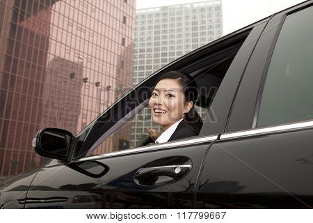 Businesswoman looking out car window