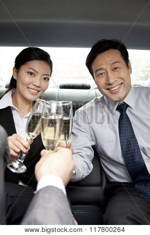 business people toasting in back of car