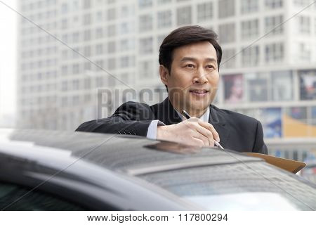 Businessman working outdoors on car