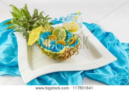 Pineapple Cut In Half With Sliced Fruit And Lemon Coctail Side View