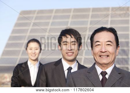 Three Businesspeople in front of Solar Panel