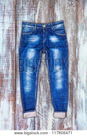 Jeans trouser over dark wood planks background