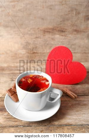 Cup of fruit tea with red heart and piece of chocolate on wooden background closeup