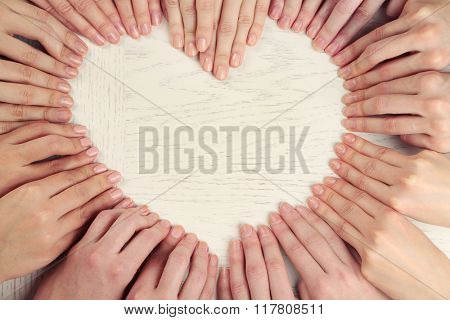 A lot of fingers making heart shape on wooden background