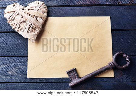 Old key with decorative heart and sheet of paper on dark wooden background, close up