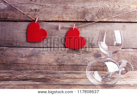 Red hearts with wine glasses on wooden background