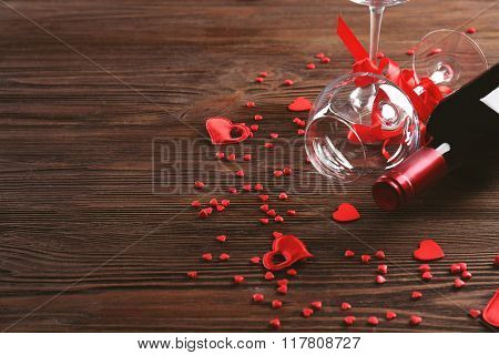 Wine bottle and glasses with handmade hearts on wooden background