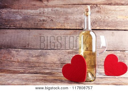 Red hearts with wine bottle and glasses on wooden background
