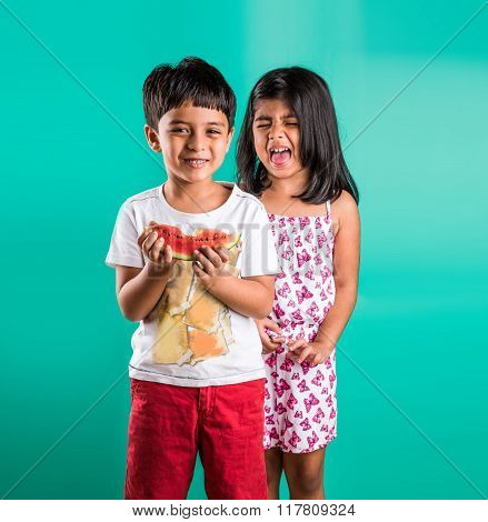 two indian kids fighting for watermelon, indian baby girl and indian baby boy fighting for fruit