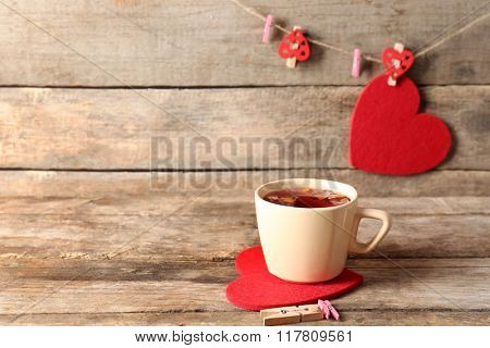 Cup of tea on red heart with clothespins on wooden background closeup