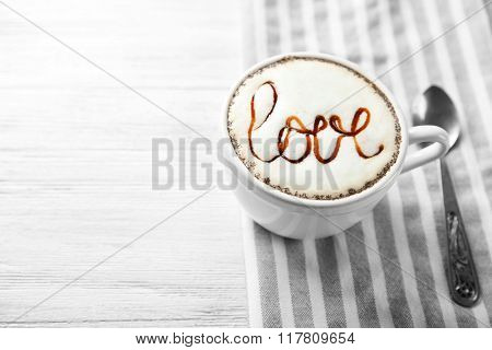 Cup of cappuccino with chocolate syrup and candy on light wooden table