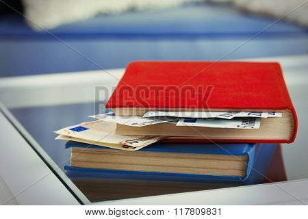 Red and blue books with hidden euro banknotes on glass table