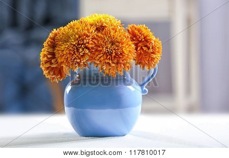 Vase of orange chrysanthemums on table