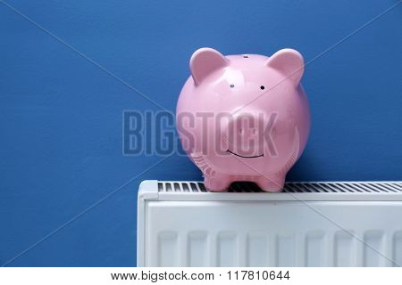 Piggy bank on radiator. Saving  heating in winter