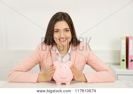 Happy young woman holding piggy bank with inserted dollar banknote. Money savings concept