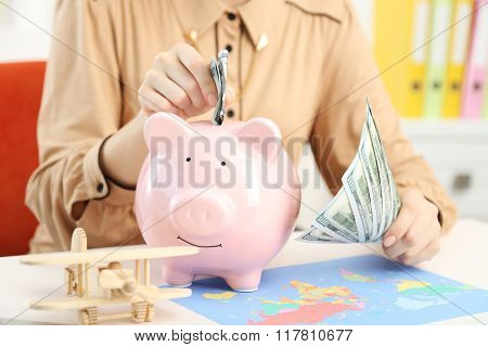 Woman putting dollar banknotes into piggy bank. Savings money for travel concept