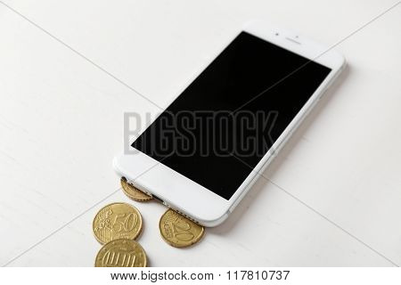 Smart phone and euro coins on light table. Telephone charges