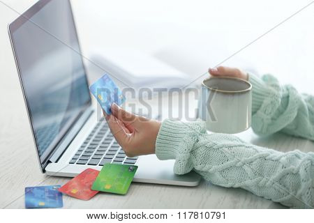E-commerce concept. Woman with credit card, laptop and cup of coffee, close up
