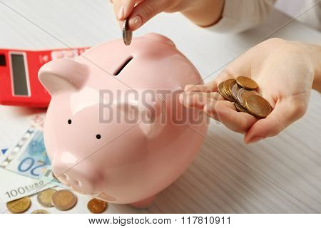 Woman's hands putting euro coin into a piggy bank on the table. Financial savings concept
