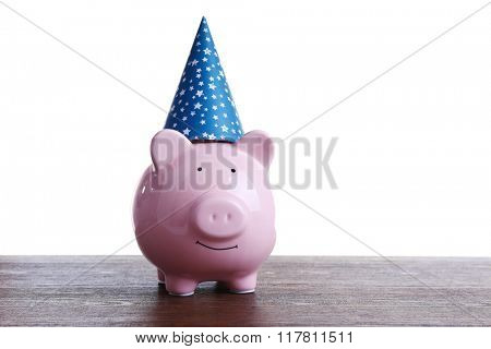 Piggy bank with birthday hat wooden table, on white background