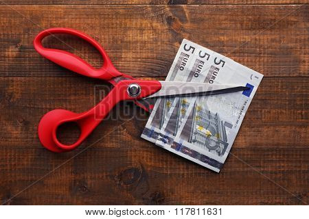 Scissors cuts euro banknote on wooden background