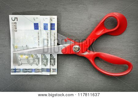 Red scissors cut money on black background. Financial concept