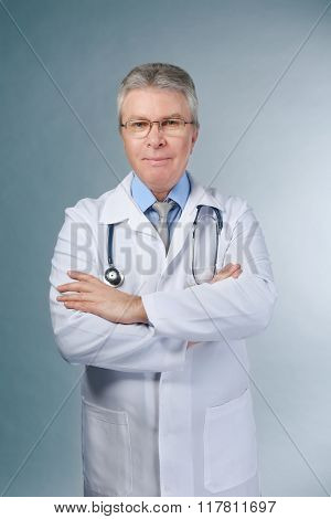 A handsome doctor with crossed arms standing on grey background