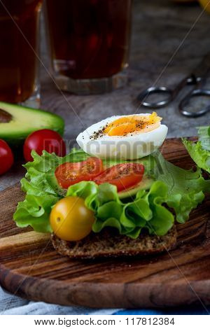 Eggs on toasted bread with ham and avocado