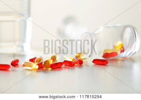 Colourful capsules spilled from pill bottle and glass of water on the table, close up