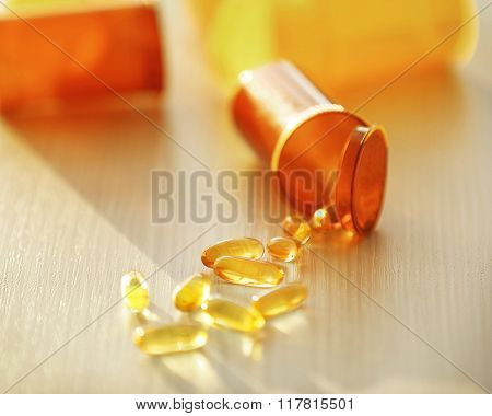 Capsules spilled from orange pill bottle on wooden table, close up