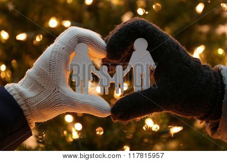 Hands holding little statuette family on lighted background