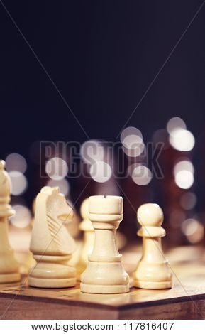 Chess pieces and game board on dark lights background
