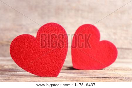 Red felt hearts on wooden background