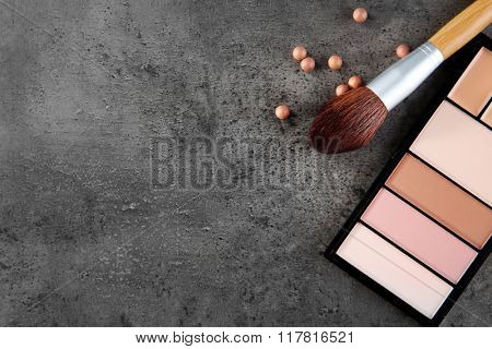 Makeup brush and cosmetics on grey background, copy space