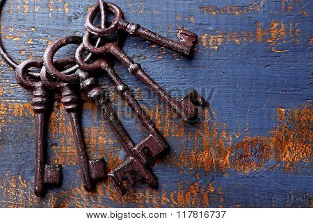Bunch of old keys on blue scratched wooden background, close up