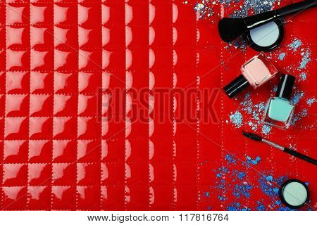 Cosmetics and makeup brushes on red background
