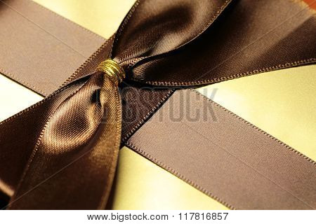 Gift box in golden wrap with brown ribbon