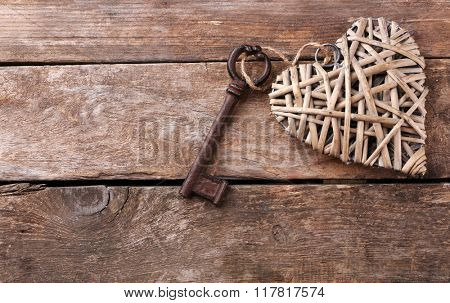 Old key with decorative heart on wooden background, close up