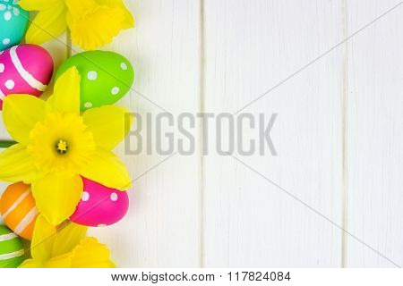 Easter eggs and daffodils side border over white wood